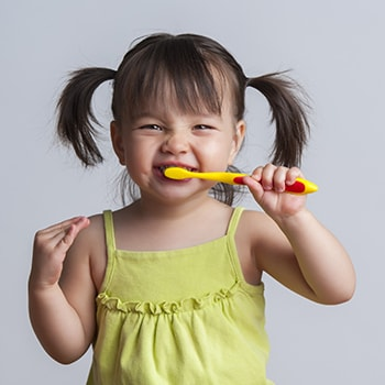Small, cute child brushing her teeth