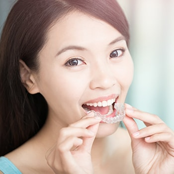 Patient putting on Invisalign aligners for a straight, beautiful smile
