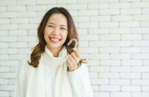 A woman holding her invisalign tray
