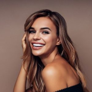 A woman in black top smiling about dermal fillers and BOTOX