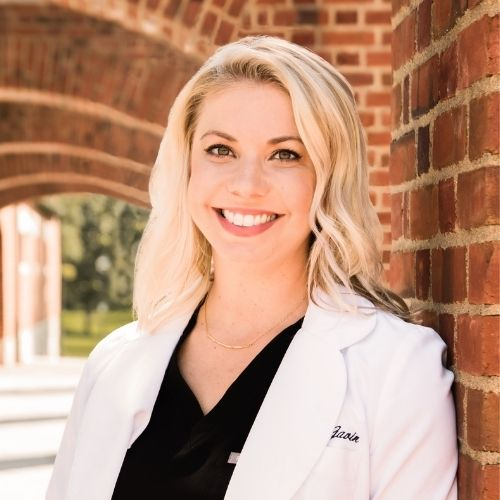 Dr. Amy Gavin in white coat and black scrubs against brick background